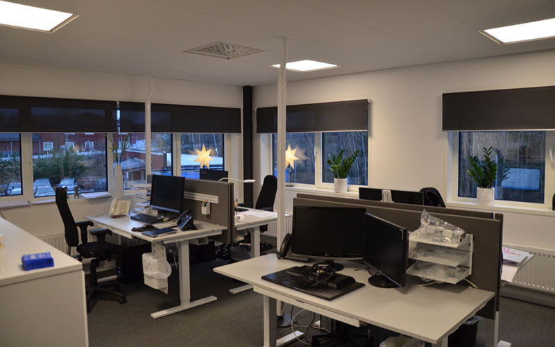 Rullgardiner monterade i kontorsmiljö.